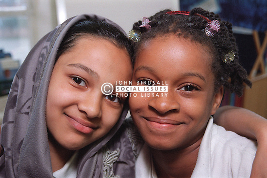 Two primary school girls standing together smiling,