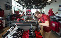 NWA Democrat-Gazette/BEN GOFF @NWABENGOFF             Austin Greek, Hog Heaven employee, sorts shirts Wednesday, Aug. 7, 2019, at the new Hog Heaven shop on the North side of Reynolds Razorback Stadium in Fayetteville.