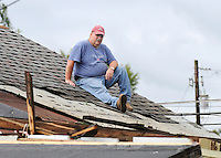 Photo By Kristin Eberts: Lee Bartlett surveys the wreckage from the rooftop of his daughters' house on Friday, Sept. 17, 2010, in The Plains, Ohio. An unconfirmed tornado ripped through The Plains, Ohio Thursday Sept. 16, 2010, causing downed power lines, uprooted trees, overturned mobile homes and significant damage to Athens High School.
