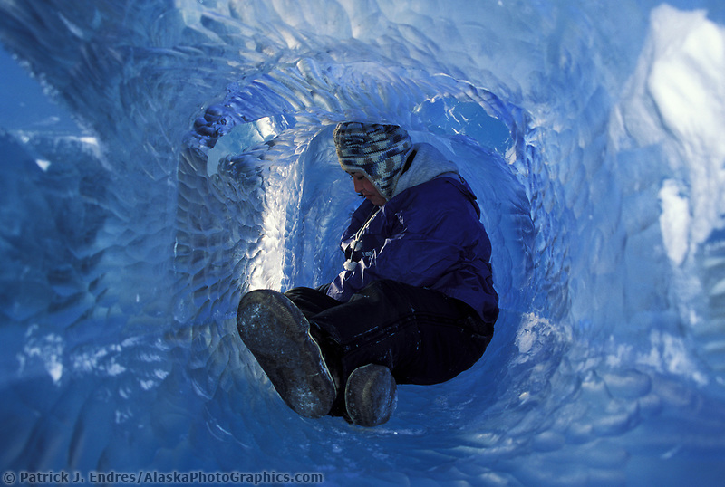 "Native Alaska ice sculptor, Brenna Outwater, chisels away inside a long ice tube, created by joining multiple blocks of ice. The Sculpture, titled ""Soul Catcher"", designed by Native artist Kathleen Carlo, won first place in the abstract category multi block competition at The 1996 World Ice Art Championships held each march in Fairbanks, Alaska."