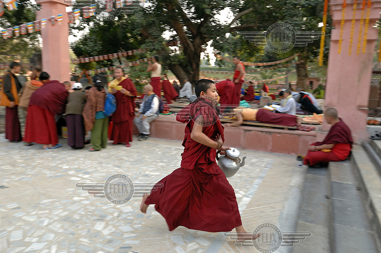 A young monk runs to fill up a pot of tea at Bodh Gaya, or Bodhgaya, a city famous for being the place of Buddha's attainment of Enlightenment. Thousands of Buddhists from all over the world gather in front of the tree where he reached Nirvana. For Buddhists, Bodh Gaya is the most important of the main four pilgrimage sites related to the life of Gautama Buddha. Since 1953, Bodh Gaya has been developed as an international place of pilgrimage. Buddhists from all over Asia have established monasteries and temples within easy walking distance of the Mahabodhi compound.