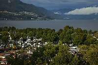 Switzerland. Canton Ticino. Tenero. View on Camping Campofelice, the Alps and Lago Maggiore. Lake Maggiore (Lago Maggiore) or Lago Verbàno is the largest lake in southern Switzerland. A campervan (or camper van), sometimes referred to as a camper, or a caravanette, is a self-propelled vehicle that provides both transport and sleeping accommodation. A motorhome (or motor coach is a type of self-propelled recreational vehicle (RV) which offers living accommodation combined with a vehicle engine. Motorhomes are part of the much larger associated group of mobile homes which includes caravans, also known as tourers, and static caravans. A caravan, travel trailer, camper or camper trailer is towed behind a road vehicle to provide a place to sleep which is more comfortable and protected than a tent. It provides the means for people to have their own home on a journey or a vacation. Campers are restricted to designated sites for which fees are payable. 21.07.2018 © 2018 Didier Ruef