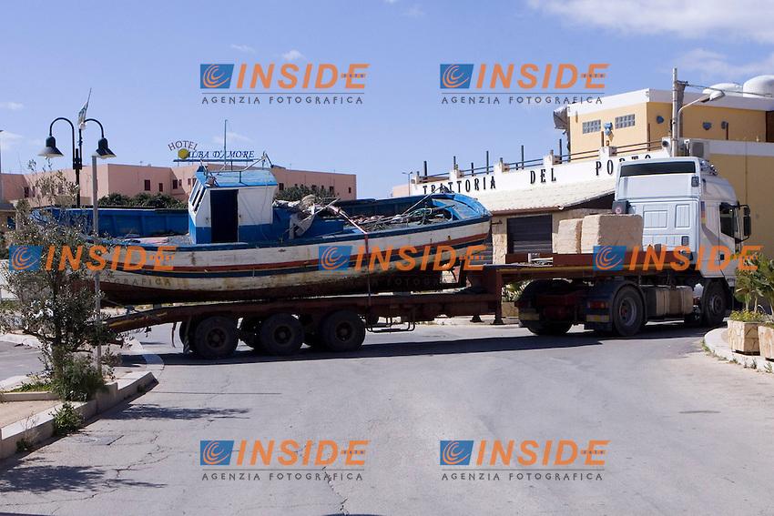 Il barcone arrivato nella notte tra il sette e l otto marzo viene caricato su un camion e trasportato nella base Nato sull isola in attesa di essere smaltito...I barconi che trasportano i profughi vengono depositati in tre punti dell isola in attesa di essere smaltiti. ..Lampedusa 09 Marzo 2011...Photo Serena Cremaschi Insidefoto..........