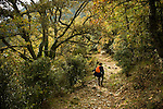 A woman hiking along a path in Corsica, France.