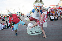 SARANSK, RUSSIA - June 25, 2018: Two  fans post with a statue of Zabivaka, the mascot of the 2018 World Cup, in Millennium Square in Saransk before the 2018 FIFA World Cup group stage match between Iran and Portugal at Mordovia Arena.