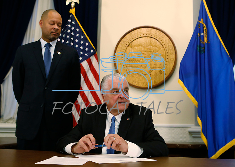 With newly sworn Attorney General Aaron Ford at his side, Nevada Gov. Steve Sisolak signs his first executive order calling for a task force to address sexual harassment at the Capitol, in Carson City, Nev., on Monday, Jan. 7, 2019. (Cathleen Allison/Las Vegas Review-Journal)