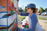 NWA Democrat-Gazette/DAVID GOTTSCHALK  Jessie Ward, an artist from Fayetteville, paints mural for the City of Fayetteville on a traffic control box Friday, September 18, 2015 in at the intersection of Arkansas Avenue and Maple Street in Fayetteville. Ward is painting an Autumn woods scene. Several artists are working to paint the different boxes in the Fayetteville area to help create unique works of art and also to help discourage the boxes from being covered with graffiti.