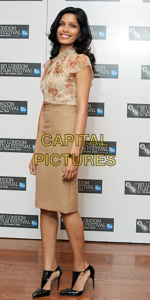 FREIDA PINTO  .The 'Miral' press conference & photocall, London Film Festival, Vue West End, Leicester Square, London, England..October 18th, 2010.full length beige skirt top blouse silk satin floral print ankle shoes .CAP/WIZ.© Wizard/Capital Pictures.