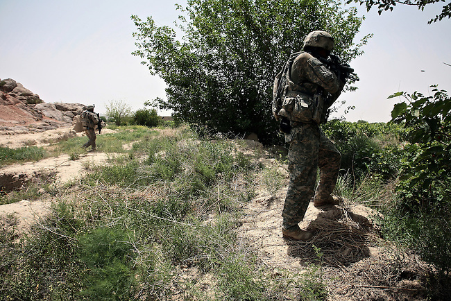 Soldiers with Company A, 2nd Battalion, 2nd Infantry Regiment return fire after their patrol is attacked by Taliban fighters near the village of Zangabad in Panjwayi district, Kandahar province, Afghanistan. April 27, 2009. DREW BROWN/STARS AND STRIPES