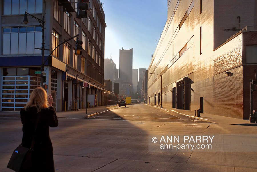 At side, Woman from back, looking down deserted Manhattan street early morning, NYC, New York, USA in 2006.