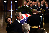 Former US President George W Bush (C) and former first lady Laura Bush walk past the casket bearing the remains of former US President George H.W. Bush at the US Capitol during the State Funeral in Washington, DC, December 3, 2018. - The body of the late former President George H.W. Bush travelled from Houston to Washington, where he will lie in state at the US Capitol through Wednesday morning. Bush, who died on November 30, will return to Houston for his funeral on Thursday. (Photo by Brendan SMIALOWSKI / AFP)