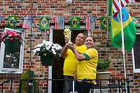 Danbury, CT - Thursday, June 12, 2014: Brazillian Joao Oliveria and his wife Elaine hold a replica of the World Cup trophy at their home in Danbury, CT during halftime of the Brazil vs. Croatia World Cup opening match.