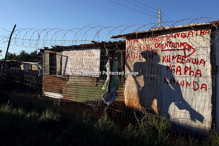 A young woman's shadow appears massive on a wall just before sunset in a shantytown outside of Johannesburg, South Africa. The barbed wire is an attempt to create some security in country with one of the highest crime rates in the world. Sexual violence is particularly prevalent and South Africa was reported to have the highest rape rate in the world for several years running in the past decade.