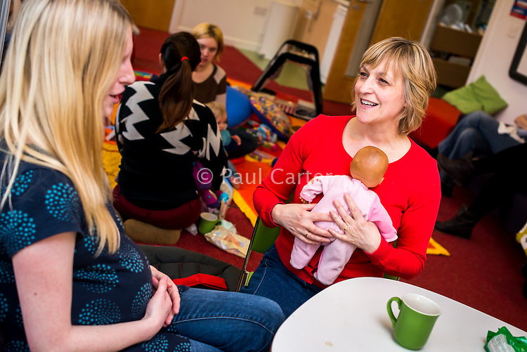 A midwife, using a doll to demonstrate, discusses breastfeeding techniques with a pregnant woman at a drop-in breastfeeding support centre.<br /> <br /> Image from the breastfeeding collection of the &quot;We Do It In Public&quot; documentary photography picture library project: <br />  www.breastfeedinginpublic.co.uk<br /> <br /> Hampshire, England, UK<br /> 13/03/2013<br /> <br /> &copy; Paul Carter / wdiip.co.uk