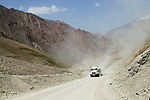 Mining trucks driving on mountain road, eastern Kyrgyzstan