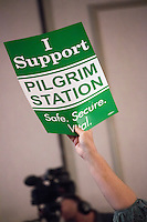 "Mary Gatslick, of Plymouth, Mass., holds a sign reading ""I support Pilgrim Station / Safe. Secure. Vital"" at a public hearing regarding Pilgrim Station, a nuclear power plant run by Entergy, at Hotel 1620 in Plymouth, Massachusetts, USA, on Tues., Jan. 31, 2017. Gatslick was one of few at the meeting expressing support for the power plant's continued operation. She says she has worked for Entergy for 25 years. ""I am totally insulted by remarks about the incompetence of workers [at Pilgrim Station],"" she said. An email from the NRC was leaked in December 2016 outlining problems with the ""safety culture"" at the plant and an ""overwhelmed"" staff. Area residents have been calling for the plant to be shut down. The green signs in the audience, reading ""Shut Pilgrim Now,"" are from a group of area residents calling for the plant's closure called Cape Downwinders."