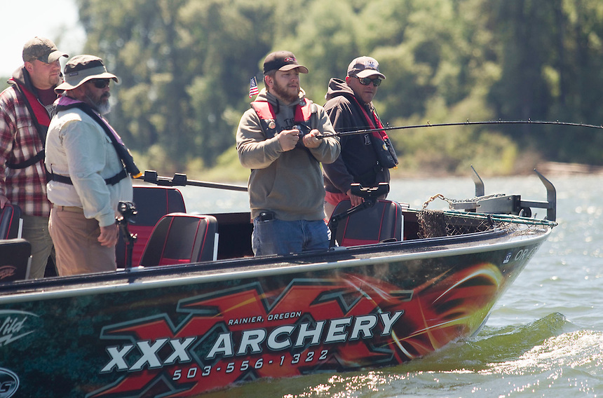 Veteran Jason Royse reels a line in as he takes part in the annual Operation Salmon Salute along the Columbian River north of Ridgefield Sunday June 26, 2016. The event hosts veterans for a day of fishing. Royse is joined by other veterans (L to R) Matt Wirkkla, Anthony Cavenaugh, and Jason Dodge. (Photo by Natalie Behring for the Columbian)