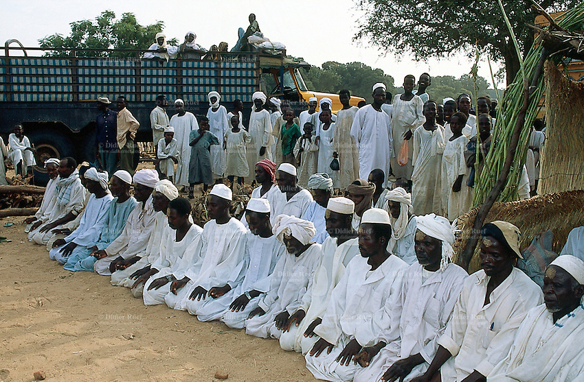 Sudan. West Darfur. Kerenek. Seating on their on the ground according to the islamic tradition, a group of men, dressed in white clothes with a turban on the heads, pray in the afternoon during the ramadan time. © 2004 Didier Ruef