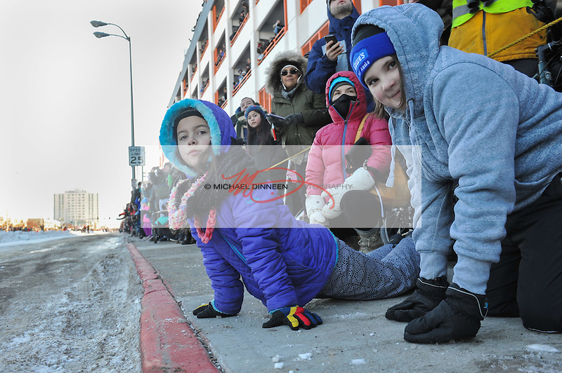 From left, Nayla Timmer, 8 and Delayna Barnum, 12  of Chugiak find a lower angle helps their view of dogs and mushers during the ceremonial start of the 45th Iditarod Trail Sled Dog Race in Anchorage, Alaska Saturday, March 4, 2017.