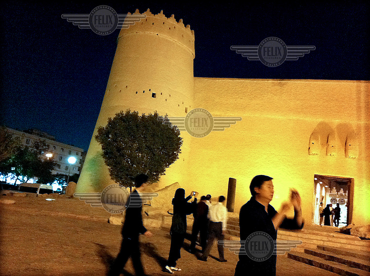 A group of foreigners take photographs with mobile phones while visiting Al Masmak Fortress.