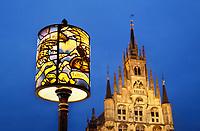 Nederland - Gouda - December 2018. Rond de feestdagen in december hebben de lantaarpalen in Gouda een lampenkap met een dessin van een gebrandschilderd raam. Op de achtergrond het oude Stadhuis.   Foto Berlinda van Dam
