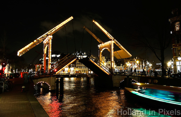 Amsterdam. Ophaalbrug over de Nieuwe Herengracht.  De brug staat open. Light Festival Amsterdam. Een rondvaartboot vaart langs de kunst objecten