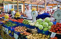 Man selling fruit and vegetabkes in indoor market, Lviv, Ukraine