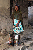 In the village of Sangrampur, a young girl carries electronic waste, which she will deliver to her family nearby who recycle e-waste as a source of income. Kolkata, India. November, 2013