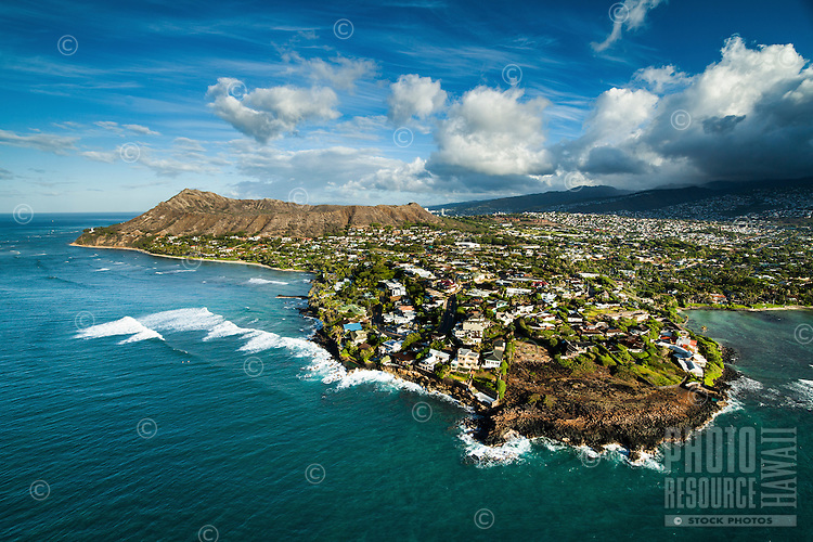An aerial image of Black Point and Diamond Head at sunrise on O'ahu, with surfers waiting in the ocean beyond the big waves that rush towards the Shangri La estate.