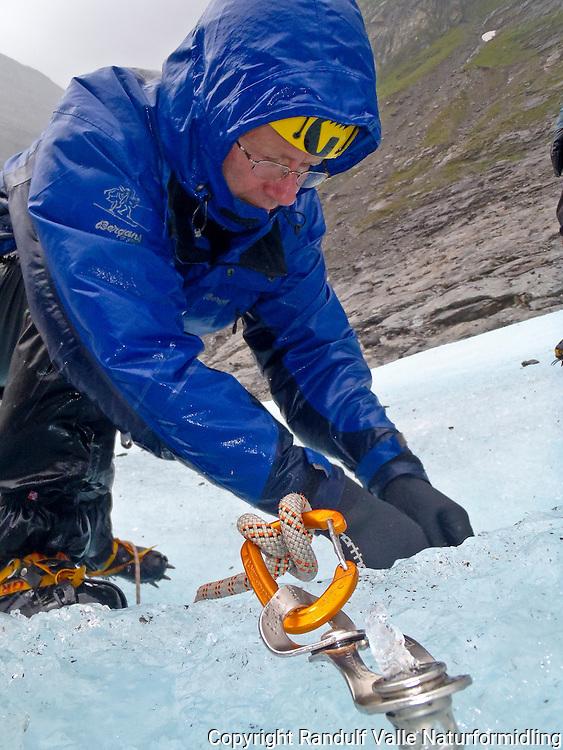 Mann jobber med isskrue og tau på isbre en våt sommerdag. ---- Man on glacier a rainy day.