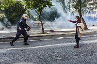 A riot police officer approaches a woman during a protest by teachers that led to clashes with riot police in Athens