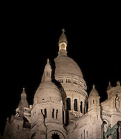 Sacré-Coeur Basilica, Paris, France, 1884-1914, Paul Abadie. A low angle view of the Basilica at night, showing the clustered white domes against a deep black night sky. Built in white travertine on the top of the Butte de Montmartre, the Romano-Byzantine style Sacré-Coeur was designed as a monument to those who died in the Paris Commune during the Franco-Prussian War, 1870-71. Picture by Manuel Cohen