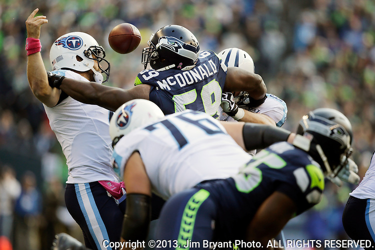 Seattle Seahawks defensive tackle Clinton McDonald (69) knocks the ball out as he pass rushes Tennessee Titians quarterback Ryan Fitzpatrick (4) at CenturyLink Field in Seattle, Washington on  November October 13, 2013. The Seattle Seahawks beat the Titians  20-13.   ©2013. Jim Bryant Photo. All Rights Reserved.