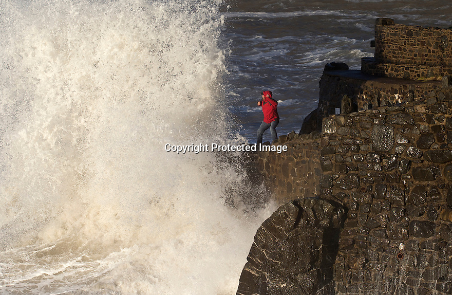 08/04/16 <br /> <br /> A man struggles to dodge giant waves at Hartland Quay, North Devon, as strong winds and high tides help to set the dramatic scene.<br /> <br /> <br /> All Rights Reserved: F Stop Press Ltd. +44(0)1335 418365   +44 (0)7765 242650 www.fstoppress.com