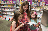 NWA Democrat-Gazette/CHARLIE KAIJO Jolie Arnold, 7, Pilar Kochel, 9 and Rumi Kochel, 6, of Cave Springs (from left) read a book during the Scholastic Book Fair, Thursday, June 6, 2019 at the 21c Hotel in Bentonville<br />