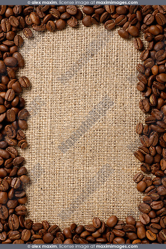 Vertical frame made from aromatic coffee beans on sacking fabric background.