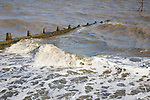Breaking waves in choppy murky brown sea water carrying heavy sediment load, Dovercourt, Harwich, Essex, England
