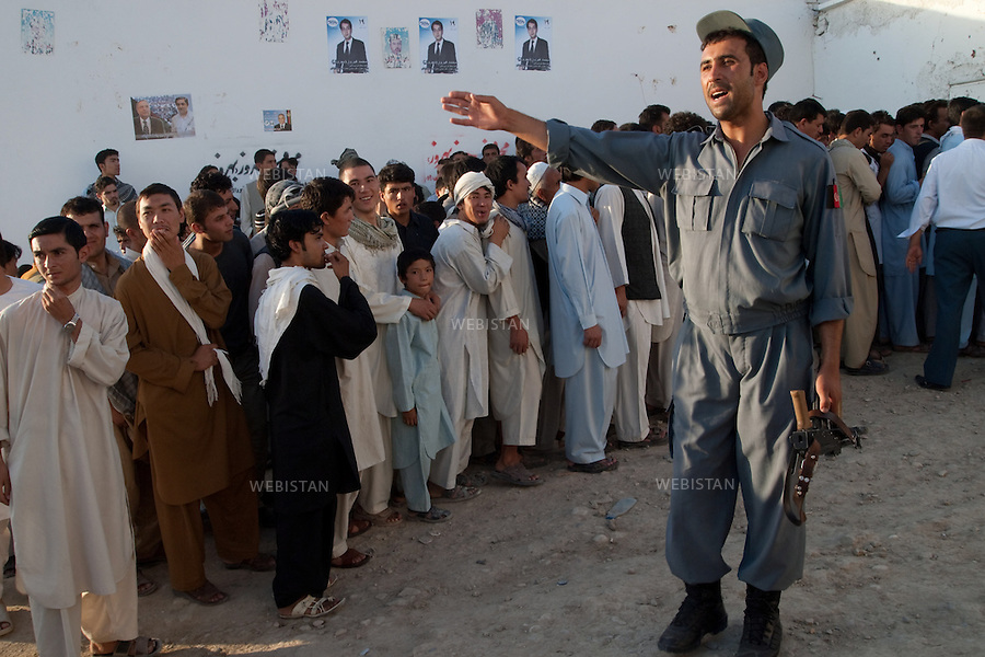 AFGHANISTAN - MAZAR-E CHARIF - 7 aout 2009 : Stade de Mazar-e Charif. Policier afghan encadrant la foule a l'entree du stade, avant le concert gratuit du chanteur afghano-americain, Farhad Darya. ..AFGHANISTAN - MAZAR-E CHARIF - August 7th, 2009 : Mazar-e Charif stadium. An Afghan police officer directs the crowd at the entrance to the stadium, where Afghan-American singer Farhad Darya will give a free concert.