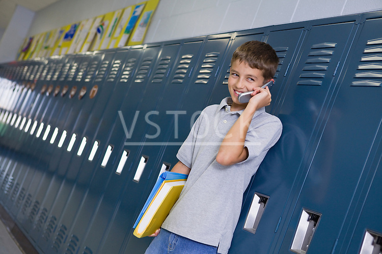 USA, Illinois, Metamora, Boy (10-11) standing at lockers in school corridor and talking on mobile phone