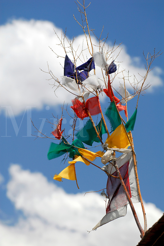 Prayer flags, flying in the breeze, dispersing their inscribed prayers, or mantras, for peace and compassion to the world, on a roof in Lhasa, Tibet.  A pre-Buddhist, Bon shamanistic tradition, the five flag colors represent blue for sky, white for clouds, red for fire, yellow for earth, green for water.