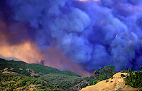 870000033 fire fighting plane and heilicopter emerge from a giant smoke cloud over an uncontrolled wildfire in the simi hills above chatsworth in los angeles county california