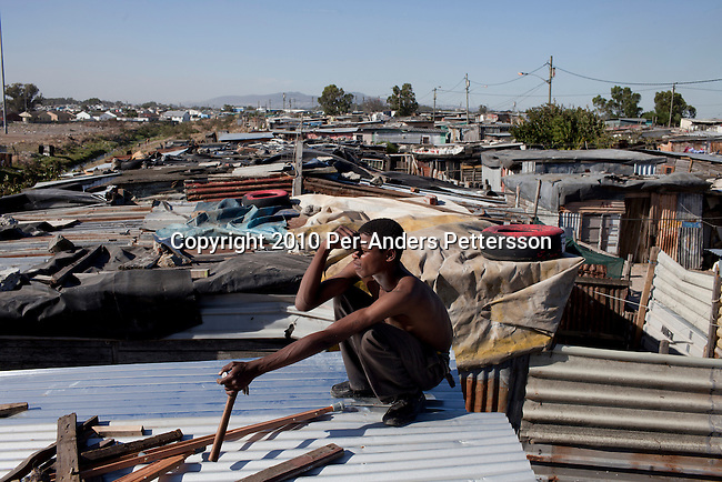 GUGULETU, SOUTH AFRICA - DECEMBER 14: A unidentified man repairs the roof on his tin shack on December 14, 2010, In the Barcelona section of Guguletu, a township outside Cape Town, South Africa. Guguletu is one of the biggest black townships in Cape Town and it was here where where British honeymooners Anni Dewani, 28, and Shrien Dewani, 31, were attacked. Anni Dewani was found with bullets in her chest in the back of the taxi after the newly weds were ambushed whilst traveling near a notorious settlement known as Barcelona. (Photo by Per-Anders Pettersson/Getty Images)