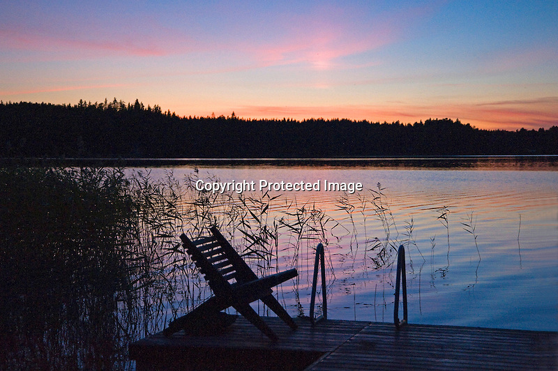Quiet Dock Silhouetted by Colorful Sunset during Finland Summer