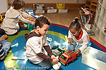 Education preschool 3-4 year olds boy and girl playing separately with plastic toy vehicle and airplane horizontal