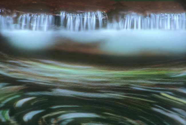 A close up section of the base of Adams Falls in Rickett's Glen State Park makes for an abstract view of swirling water and red rock