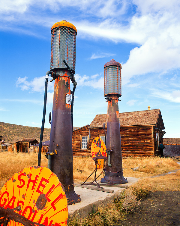Shell Gasoline pumps outside the Boone Store and Warehouse with the Lottie Johl House in the background. One of fewer than 170 structures remaining in the ghost town of Bodie; gold discovered here in 1859. Designated National Historic Landmark in 1961; 1962 it became Bodie State Historic Park. Bodie named California's official state gold rush ghost town. Historic District, California State Park. Mono County, CA.