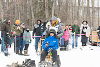 Wade Marrs and team run past spectators on the bike/ski trail near University Lake with an Iditarider in the basket and a handler during the Anchorage, Alaska ceremonial start on Saturday, March 7 during the 2020 Iditarod race. Photo © 2020 by Ed Bennett/Bennett Images LLC