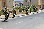 Israeli soldiers confront stone throwing Palestinian youths following a demonstration against Israel's controversial separation barrier on the main road through the West Bank town of Beit Jala near Bethlehem on 04/07/2010.