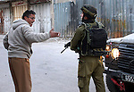 Palestinian man argues with Israeli soldier during clashes with Palestinians in the city center of the West Bank town of Hebron on February 12, 2010. Israeli troops shot and killed Palestinian Fazey Faraj, 41, as he tried to stab a soldier, the army said, only days after a Palestinian policeman stabbed a soldier to death. The shooting came as Palestinian and Jewish settlers clashed nearby and hurled stones at one another. Photo by Najeh Hashlamoun