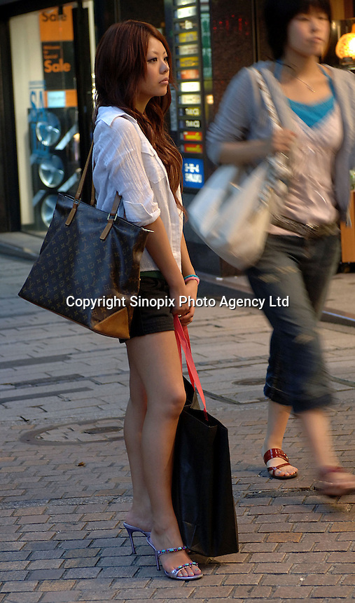 A lady shopper with a LV bag waits on a side street of a the Shinjuku shopping district in Tokyo, Japan..